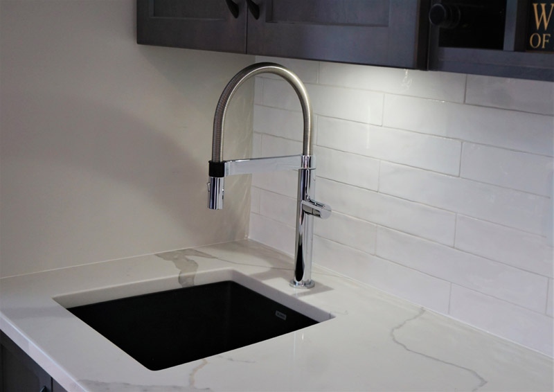 Horizontal subway style backsplash with marble countertop and bar sink.