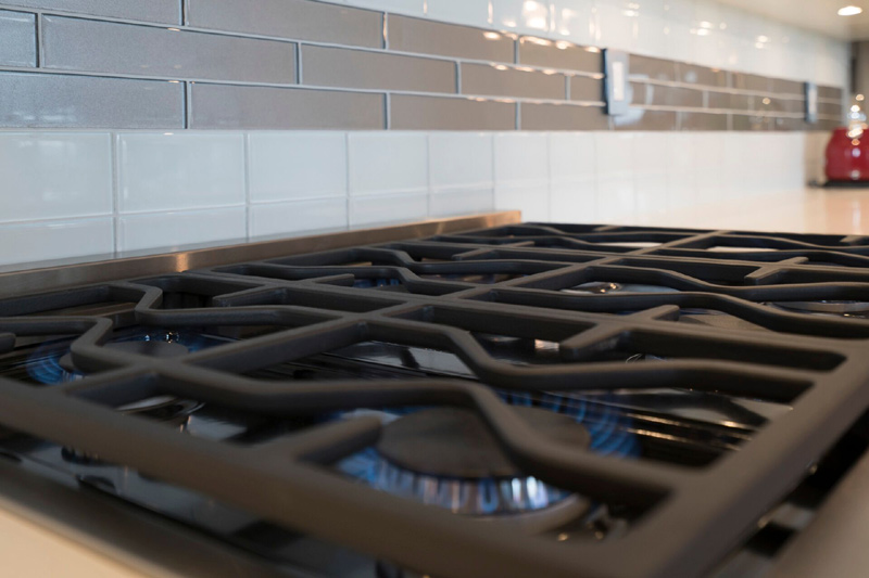 Beautiful but simple glass tile backsplash adds a touch of class to this kitchen design.