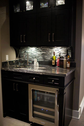 Sleek bar with metal/stone backsplash.